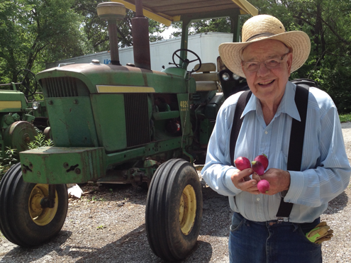 Joe standing in front of a tractor while wearing a hat and suspenders and holding radishes