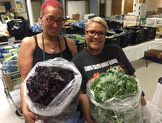 Two women holding bags of green and purple lettuce