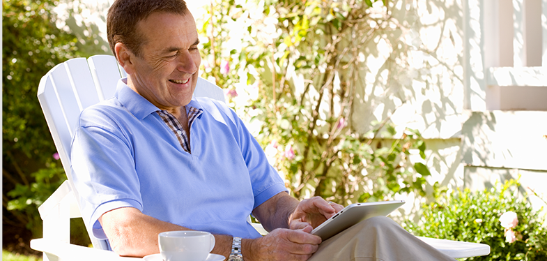 Man sitting outside on a lawn chair using an ipad sitting next to a cup of coffee